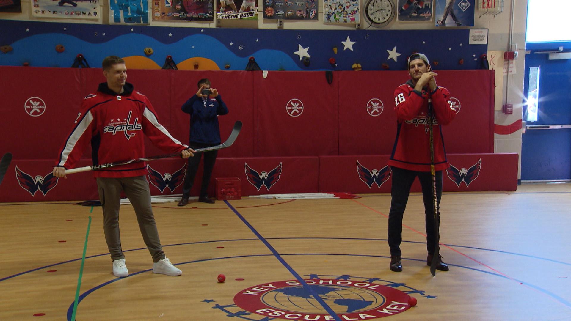 Evgeny Kuznetsov and Nic Dowd show off hockey skills at a local school